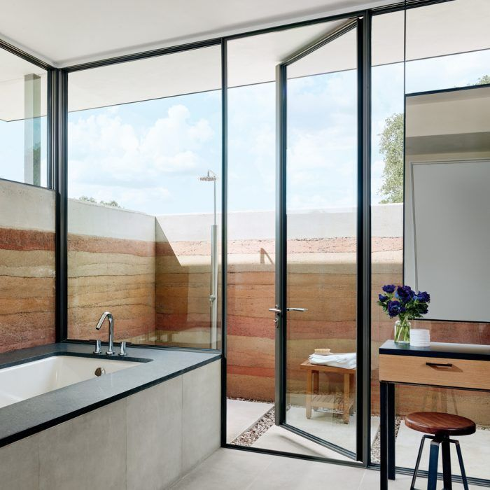 Rammed Earth Walls In The Master Bathroom Extend To Form An Outdoor Shower Enclosure Featuring Signature Hardware S Man Luxe Interiors Modern House Earth Homes