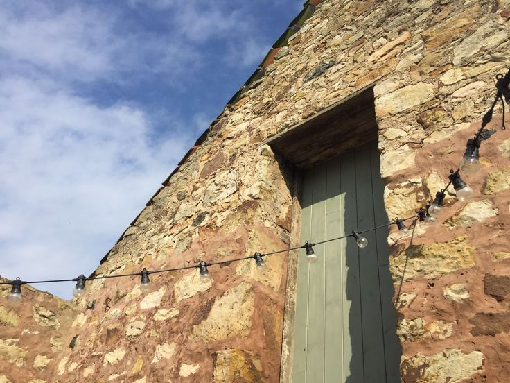 The Cow Shed Crail, Fife.  Festoon lighting and characterful stone walls at this Scottish black canvas wedding venue.