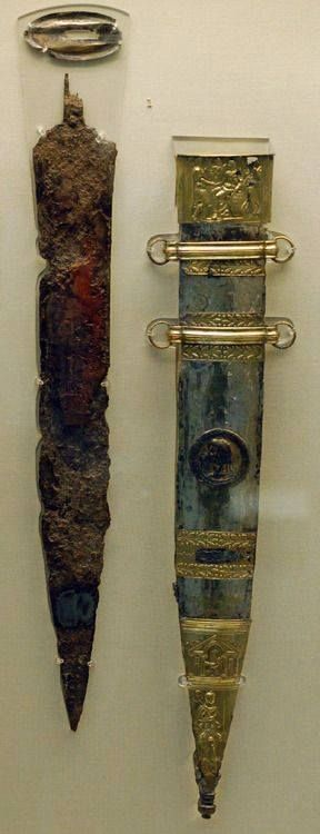 The Mainz Gladius or Sword of Tiberius is a famous ancient Roman sword and sheath that was found in the Rhine near Mainz in Germany. The length of the sword is approximately 58 cm long by 8 cm wide. The decoration on the scabbard illustrates the ceding of military victory to Augustus by Tiberius after a successful Alpine campaign. Created: 15 CE. British Museum