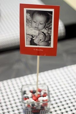 Cute table decorations with a baby photo of the birthday guy or girl.