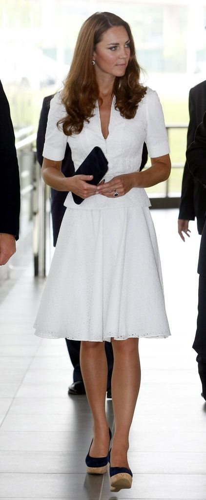 Midday, the brunette beauty stunned in a crisp white Alexander McQueen skirtsuit and navy blue Stuart Weitzman wedges. This isn't the first time Kate has worn a McQueen skirtsuit — she actually wore an ivory-hued version for the kickoff of Diamond Jubilee celebrations earlier this year. | POPSUGAR Fashion