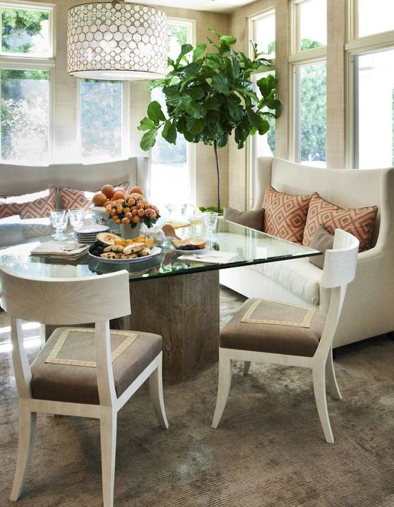 Cream and coral dining room with fiddle leaf fig plant and plenty of windows.