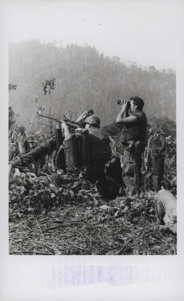 """Sniper Team, 1st Battalion, 9th Marines, 1967. """"On Target: A Marine sniper team with 1st Battalion, 9th Marines [1/9] opens fire on the enemy while participating in Operation Dewey Canyon. The multi-battalion offensive thrust in the jungles just northwest of the Ashau Valley netted the Marines 436 enemy killed during the first 30 days of the operation (official USMC photo by Lance Corporal D. L. Randolph)."""" From the Jonathan Abel Collection (COLL/3611), Marine Corps Archives."""