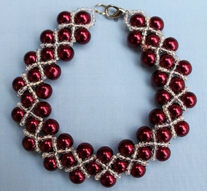 "This elegant bracelet is just right for that special evening out. It has dark cherry red pearl beads and cream lined transparent seed beads. 21cm (8½"").  Materials used: Glass and silver coloured metal."