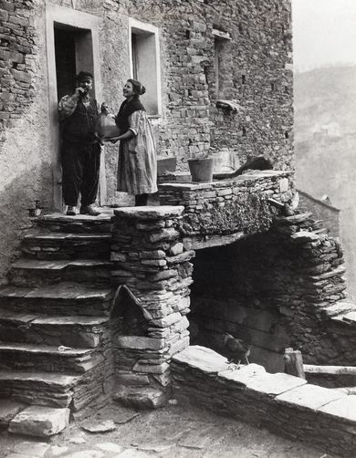 A couple hold a conversation on the front doorstep of a stone home. Piedicroce, Corsica, France.