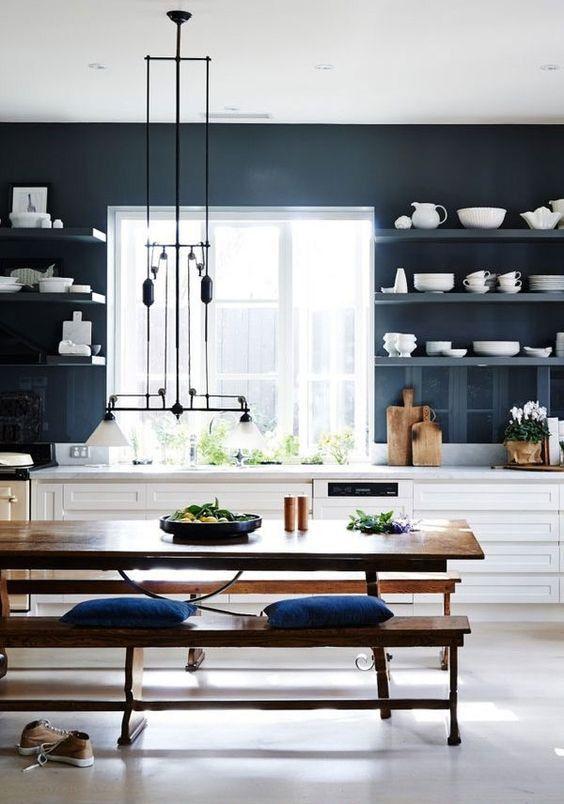 Mur bleu orage, côté fenêtre, cuisine blanche et salle à manger table en bois