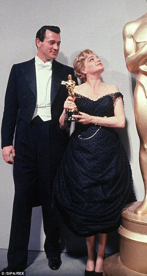 Simone Signoret, pictured here with Rock Hudson, wore a chic Jean Desses dress with a draped skirt in 1960 when she became the first French person to win an Oscar for her role in Room At The Top.
