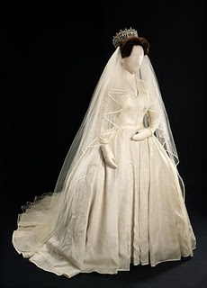 Princess Margaret's while silk organza wedding dress with a satin-bound silk tulle veil. The whole design was made to accommodate the princess's short stature, including the tiara which sat upon a hair piece to add height. The gown was designed by Norman Hartnell, who also created her sister's wedding dress.