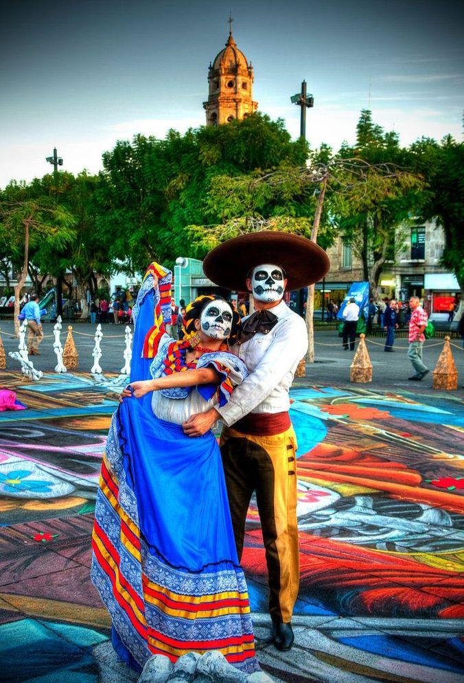 Mexicanos pintados con los motivos del Día de los Muertos con vestimentas tradicionales.
