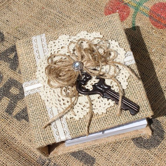 A rustic photo album is covered in natural tan burlap and layered with an ivory vintage doily, accented with jute bow, a rhinestone button and a vintage style skeleton key. Perfect for a wedding shower gift or to display all your wedding pictures, as well as would make a great gift for someone special. The album holds 120 - 4 x 6 pictures. The book measures 6 1/4 inches wide, 6 3/4 inches tall and 2 1/4 inches thick. Unlike many albums, both the outside and inside are covered, making for a…