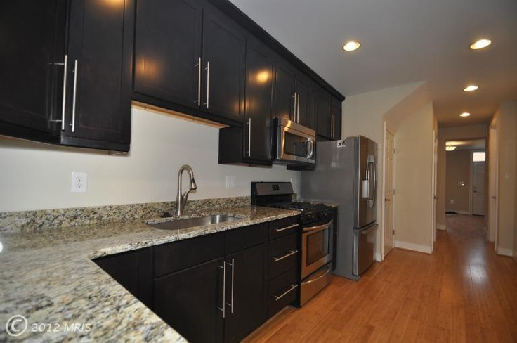 Kitchen Dark Cabinets With Tall Vertical Silver Hardware