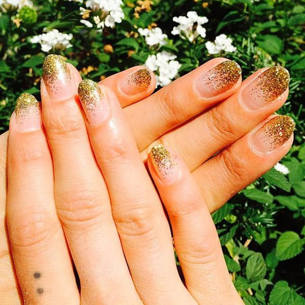 """As seen at Chi Nail Bar, glittery gold polish can get an ultra-chic update — just apply it only on the top half of each nail. No need to be careful about making straight lines — the uneven flecks give a gilded illusion that is really rad. Just """"tap"""" a glitter polish onto the tops of bare nails, then finish with a topcoat."""