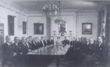 he first meeting of the Queen's Privy Council for Canada before the reigning sovereign; in the State Dining Room of Rideau Hall, Queen Elizabeth II is seated at centre, with Prince Philip, Duke of Edinburgh, to her left, and Prime Minister John Diefenbaker at her right; 14 October 1957