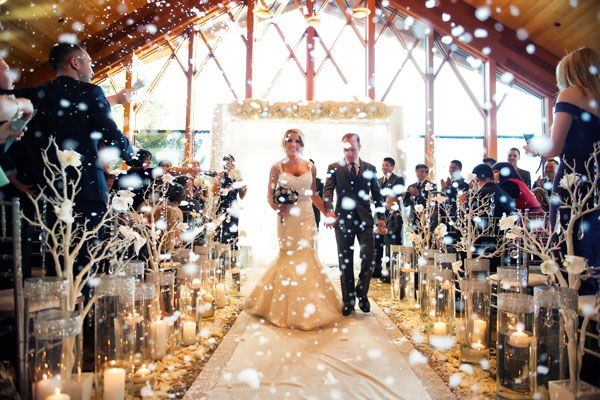 This couple transformed their ceremony into a winter wonderland complete with branches, flickering candlelight and fake snow!   FOR MORE IDEAS VISIT: http://www.candycakeweddings.com/blogs/wedding-cakes/61453957-spectacular-winter-wedding-decoration-ideas