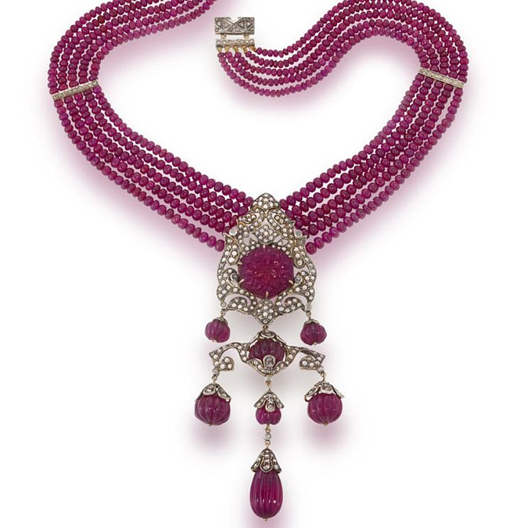 A ruby and diamond necklace  designed as five strands of graduated ruby beads accentuated by rose-cut diamond bars suspending a large openwork pendant of rose-cut diamonds which centers a hexagonal carved ruby and further fluted ruby bead fringe; mounted in silver-topped fourteen karat gold; length: 18in.  Striking!