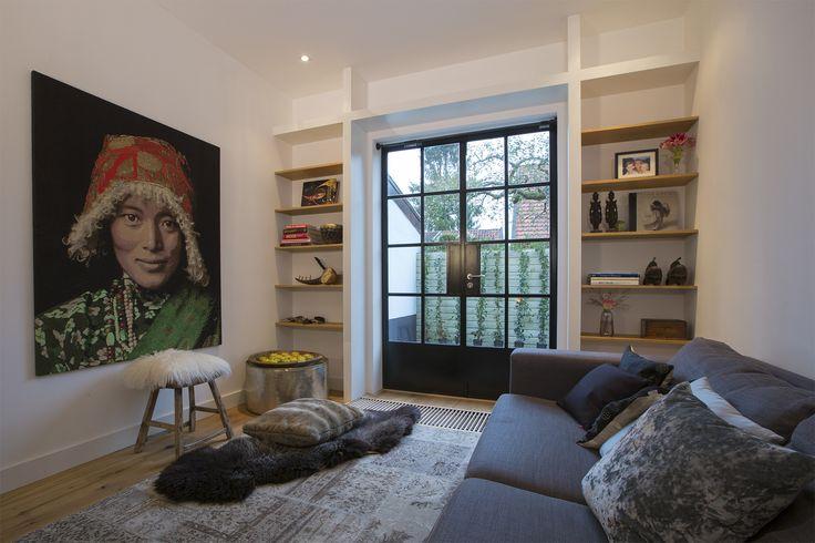 Living room with steel doors and wooden shelves