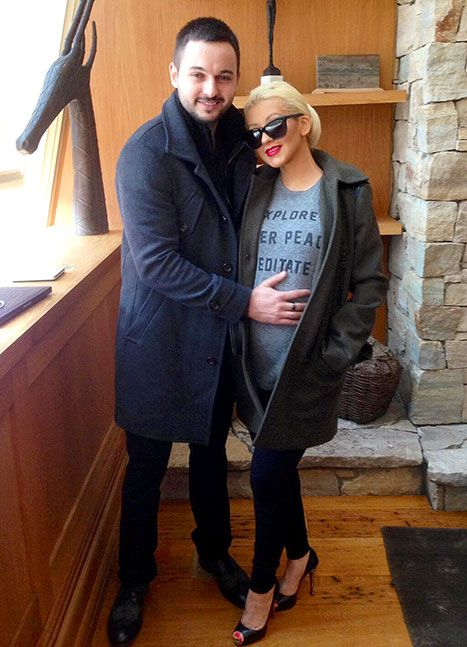 Preggo Xtina shuts it down wearing a long gray coat, shades, pumps and a bold red lip!