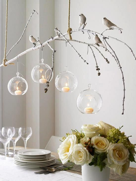 Branch and suspended glass orbs with artificial birds over table setting