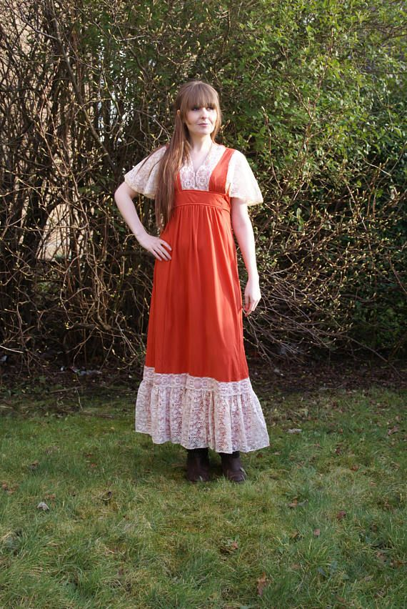 A lovely Vintage 70s Maxi Dress. Is a deep burnt orange colour with cream lace detailing on the neckline, capped sleeves and at bottom of skirt. Empire waist, ties at waist, zips up back. Perfect Summer dress! In good vintage condition. Measurements: Pit to Pit (laid flat): 16 Waist:
