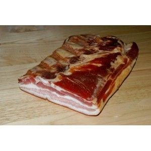 """La Pancetta Tesa Stagionata si ottiene dal tessuto adiposo sottocutaneo dell'addome del maiale, viene salata e fatta stagionare. La sua lavorazione artigianale rispecchia perfettamente le tecniche utilizzate dai nostri nonni che nel periodo """"del maiale"""" lasciavano essiccare questi prodotti appesi in casa al calore del proprio camino."""