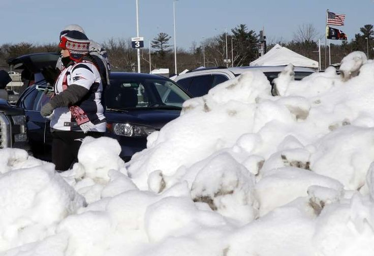 Winter Weather - FOXBOROUGH, MASSACHUSETTS -  Fans walk past a big pile of snow in the parking lot of Gillette Stadium before the game between the New England Patriots and the New York Jets, on Dec. 31, in Foxborough, Mass.
