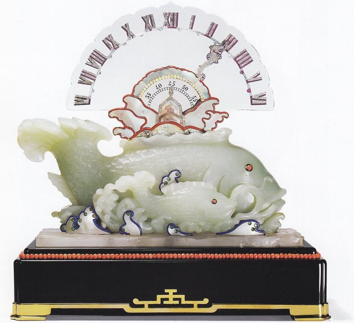 """Cartier Paris, 1925  """"Carp"""" Clock with Retrograde Hand  Platinum, gold, emerald cabochons, rose-cut diamonds,  diamonds, bbsidian, carved jade, rock crystal, coral, pearls, mother-of-pearl, black, blue and red enamel, mauve lacquer  23. 5 x 23.5 cm"""