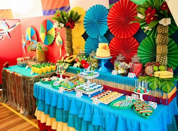 this party tablescape is so cute for any luau themed party or rio themed (just love those big paper fans as the back drop!)