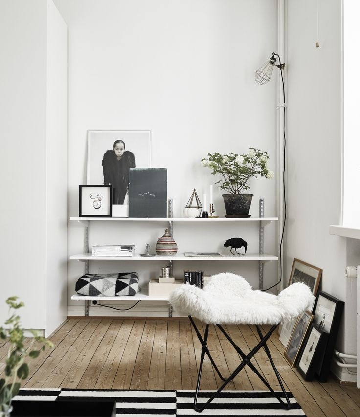 Wall hung shelves with photos, paintings and personal objects. Also a possible solution for a media wall?