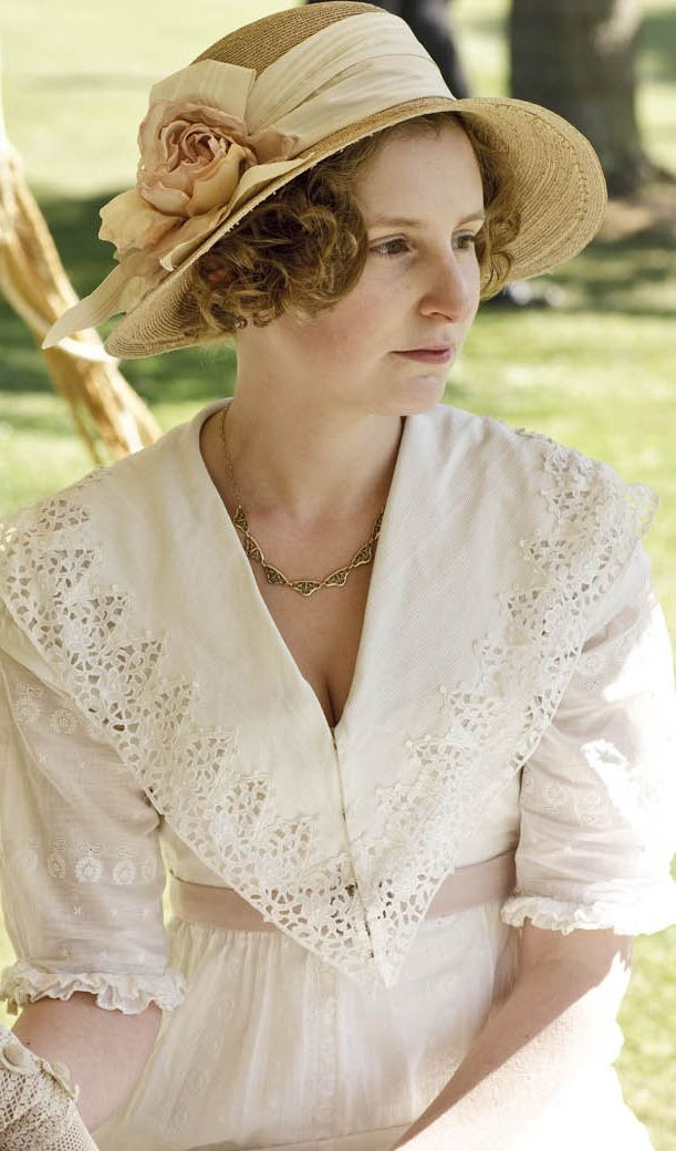 Lady Edith at a garden party in a white dress with eyelet work on the collar.  Downton Abbey