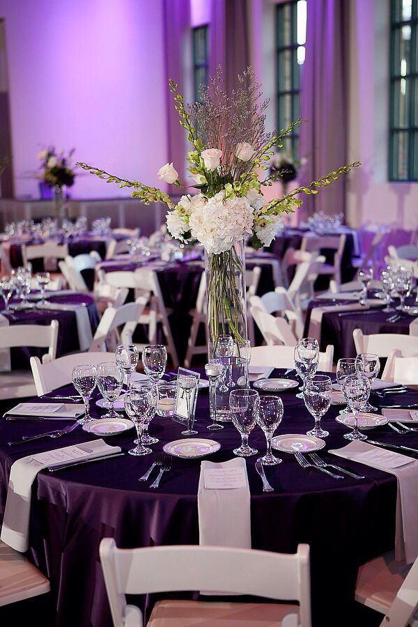 A nice visual using a Purple tablecloth, white chairs and white napkins