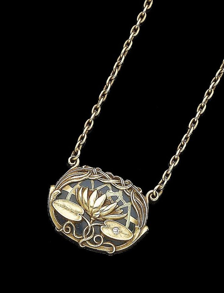 An art nouveau enamel and diamond-set pendant necklace, by Riker Brothers, circa 1910 The blue and green plique-à-jour enamel oval plaque, overlaid by a textured water lily with an old brilliant-cut diamond accent, within an interlaced textured surround, to a belcher-link chain