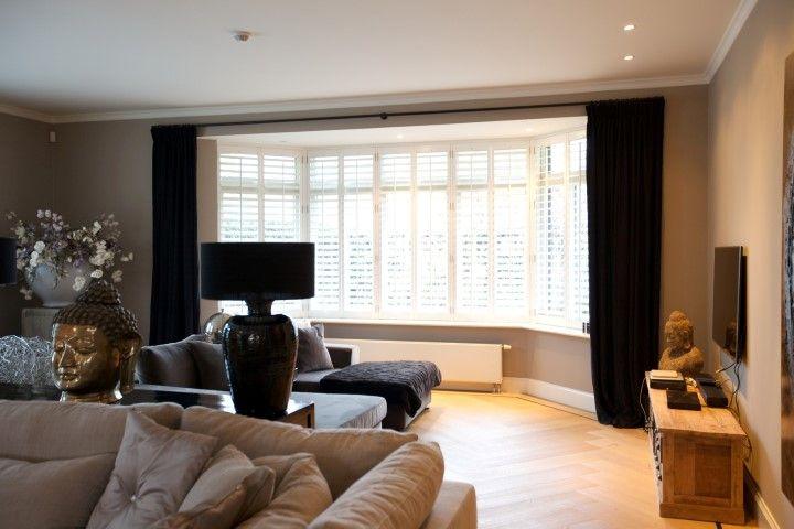 Zwarte linnen gordijnen gecombineerd witte houten jaloezieën. Ultieme combinatie van blond en donker!