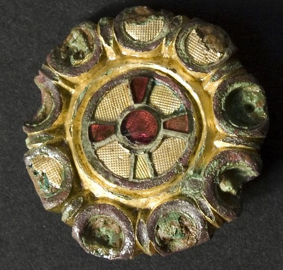 this brooch contains gold textured in a waffle shape along with a cross made of red glass and semiprecious stone