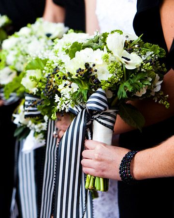 Green and white bridesmaid bouquets are cinched with chic black and white