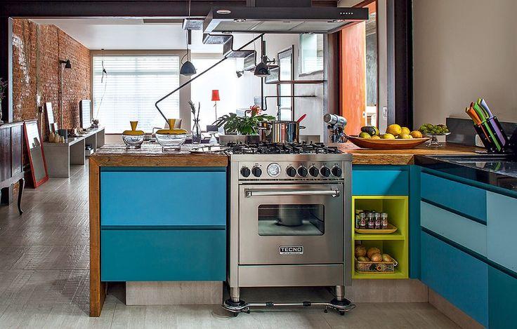 Entre os móveis azuis da cozinha, destaca-se um nicho verde néon. A solução deixou a cozinha ainda mais colorida. Projeto do escritório de a...