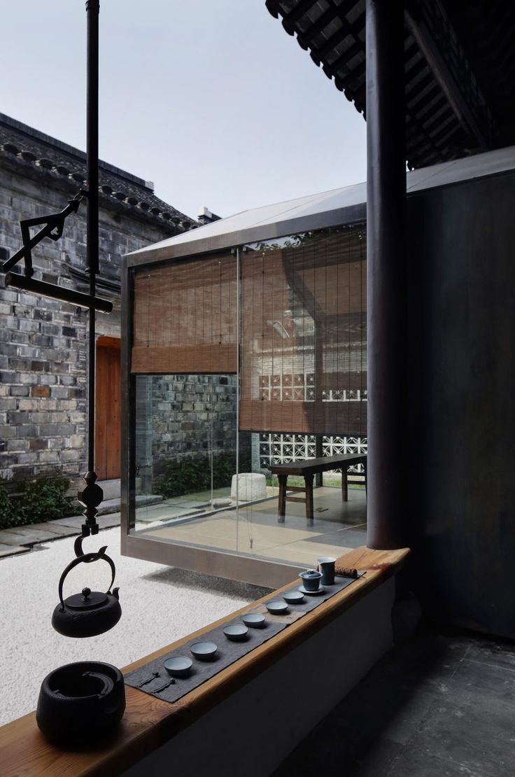 The Nanjing-based architecture studio added the gabled meditation room, which features glass walls, to the centre of the heritage-listed house.    The meditative space protrudes outwards and overhangs the base of the existing structure of the house, appearing as if it is suspended over a gravelled area of the courtyard.