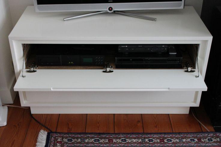 Vrijstaand TV-meubel, voorzien van een klapdeur waarachter AV-componenten en één brede lade voor CD's en DVD's. Uitgevoerd in gelakte MDF en voorzien van verlichting achter het meubel.