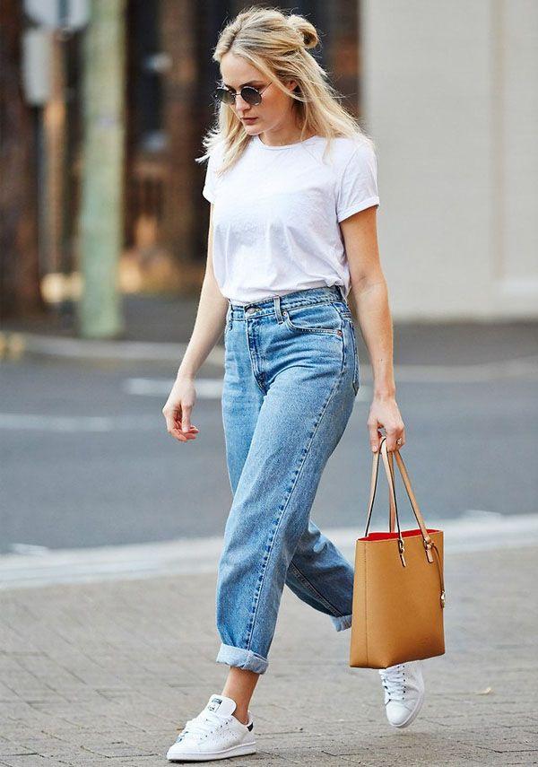 Street style de look trendy com t-shirt + calça jeans + tênis.