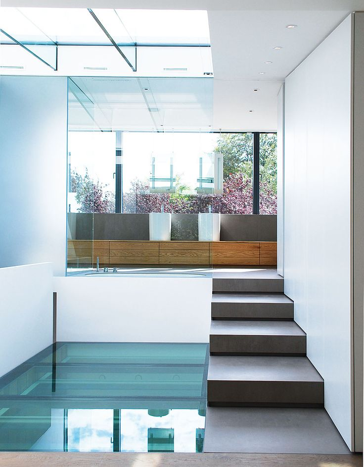 glass ceiling and floor in a hallway with concrete steps leading to bathroom