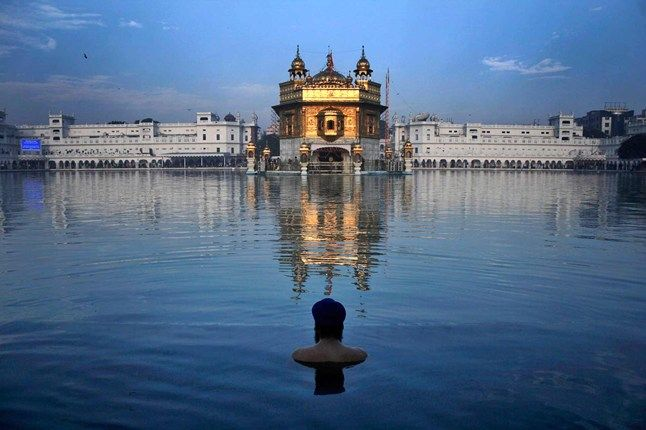 India - An Indian Sikh takes a holy bath before the sacred pond of the Golden Temple in Amritsar, India, in remembrance of Guru Nanak, the religion's founder. The temple is the Sikh's holiest and is a major pilgrimage destination. The site is also becoming increasingly popular with tourists.