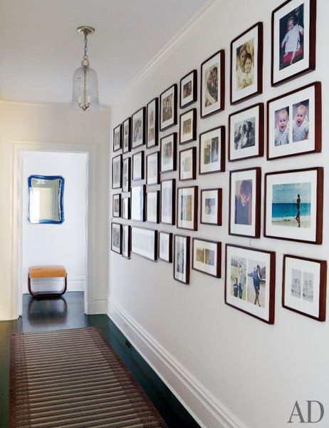 Family photos line a hallway; the striped runner is from Doris Leslie Blau.