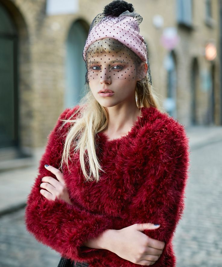 Red faux-fur cardigan worn with pink knitted hat, finished with vintage-inspired veil and bobble, all Savida by Dunnes Stores