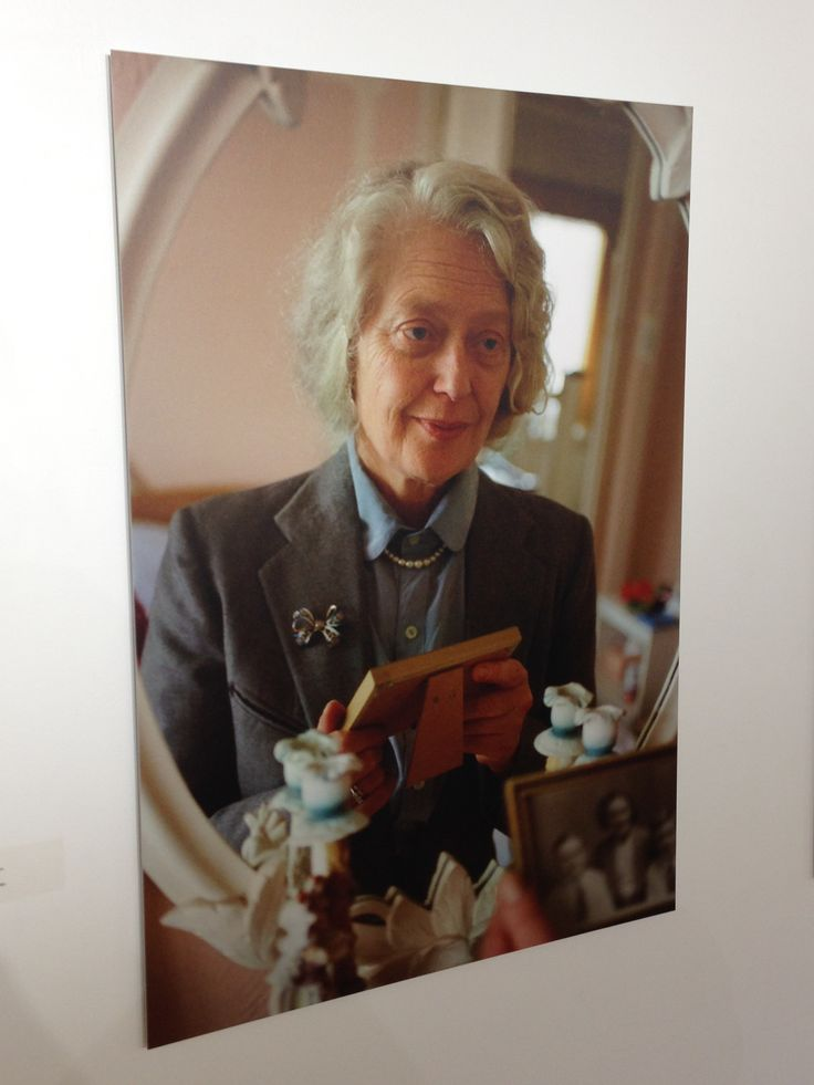 Family ties: re-framing memory exhibition: lady holding framed photo