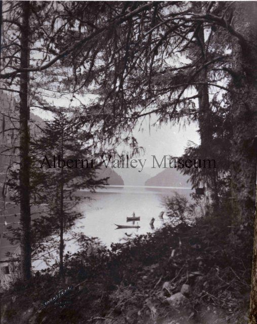 Scenic view of Great Central Lake shot through trees along the shore, 1912.  Photographer:  Leonard Frank.  [Alberni Valley Museum Photograph PN15813]