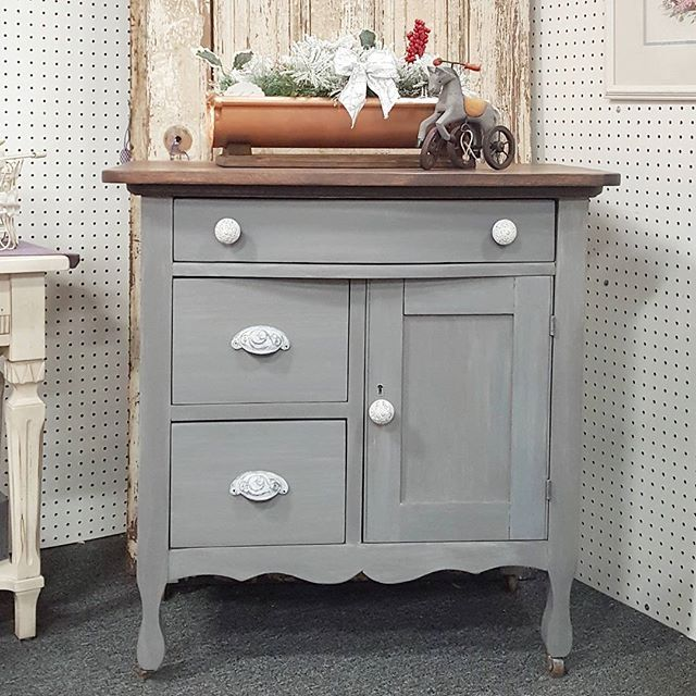 This vintage wash stand is sporting a gray stain, and gray and white washes on the base. The top got a rich brown stain and @generalfinishes High Performance Top Coat. Updated with ornate cast iron hardware. 32w x 19d x 32t. It would make a great nightstand or side table with lots of storage $327 . . . #igersgreenville #yeahthatgreenville #furniturerehabber #paintedfurniture #frenchcountry #countrycottage #countryliving #frenchcottage #farmhousestyle #farmhousedecor #smallbusiness #shoplocal…