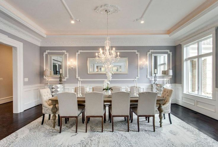 Elegant gray formal dining room with wainscoting and crystal chandelier