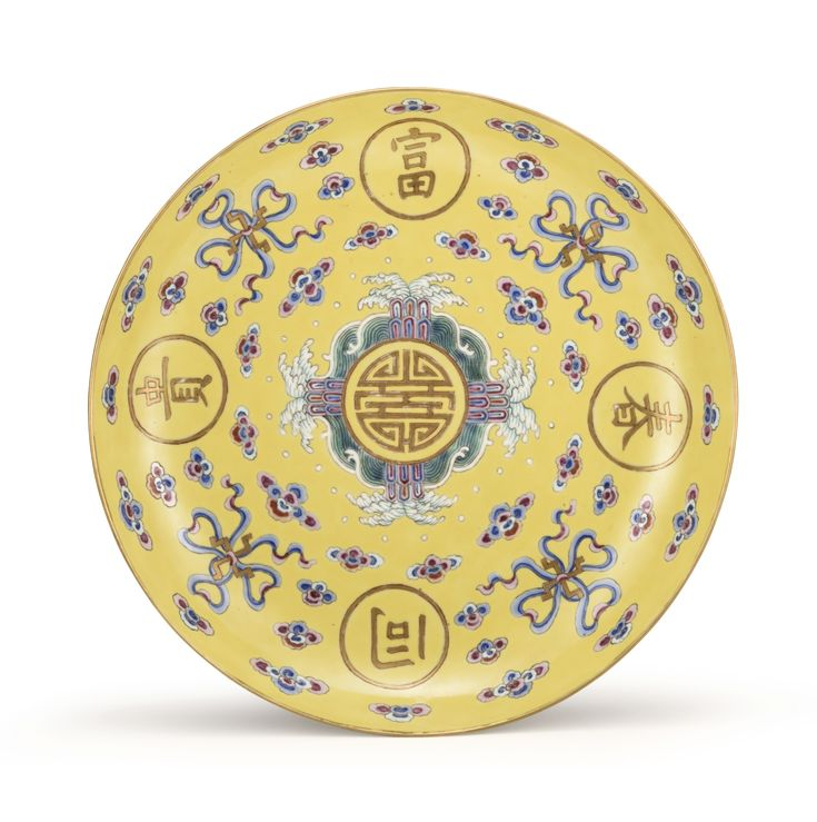 A YELLOW-GROUND FAMILLE-ROSE 'FUGUI TONGCHUN' DISH, MARK AND PERIOD OF TONGZHI centred with a single character shou surrounded by green tempestuous waves crashing on stylised rocks and the four character fugui tongchun ('May your fortune flourish as spring'), interspersed with beribboned wan symbols and multicoloured clouds, all reserved on a rich yellow-ground, the reverse decorated with floral spray on a white ground and centred with an iron red four-character mark 25.5 cm