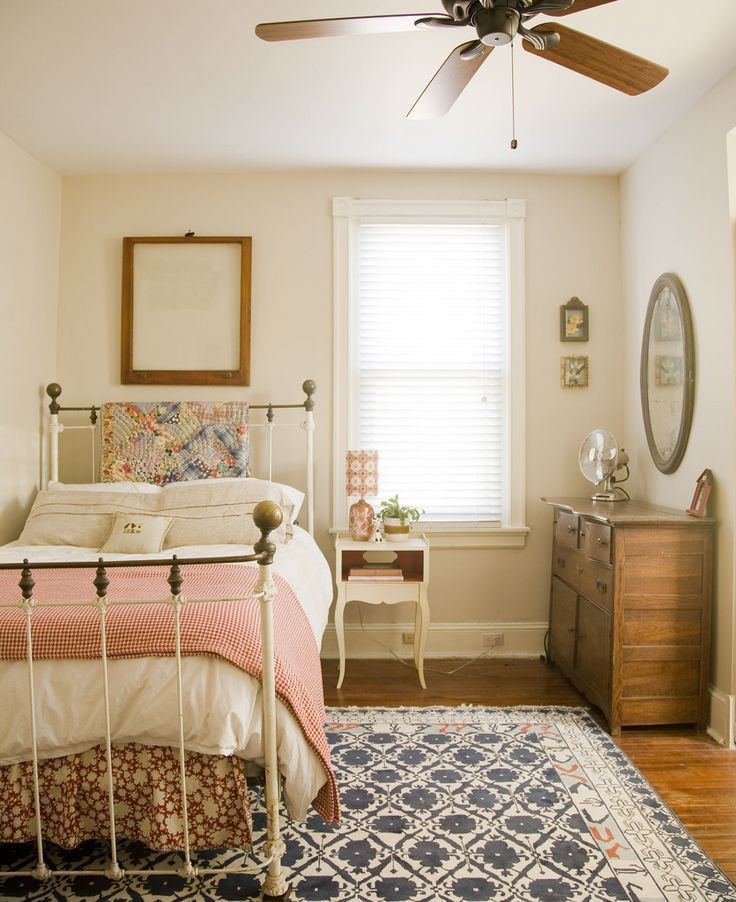 A simple cottage bedroom with a twin bed with metal frame, white night stand and wood dresser