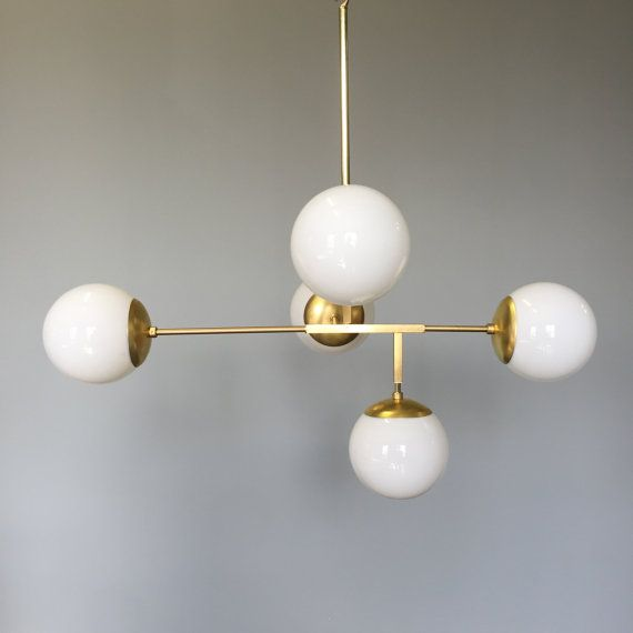 This Prisma globe chandelier is MADE TO ORDER with a typical lead time of 4 weeks. Fixture lead time can be decreased to 1 week via the following listing: https://www.etsy.com/listing/166962547. Measurements: - Length: 33 in - Width: 20 in - Height: 28 in (when installed with canopy and one 12 rod) - Weight: 7 lbs Features: - Five hand blown white glass globes (6 diameter) - Five medium base (E26) light sockets - Finishes available in brass or nickel Fixture Includes: - Simple matching ca...
