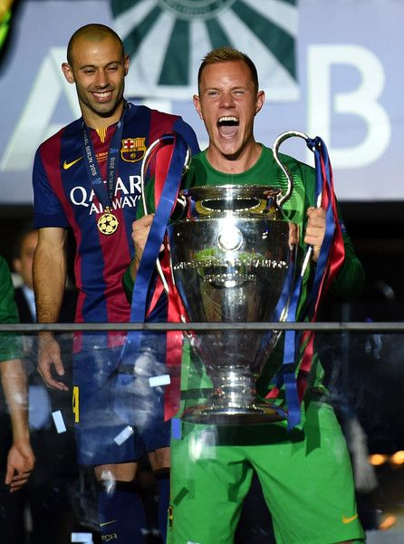 Marc-Andre ter Stegen of Barcelona celebrates with the trophy as Javier Mascherano of Barcelona looks on during the UEFA Champions League Final between Juventus and FC Barcelona at Olympiastadion on June 6, 2015 in Berlin, Germany.